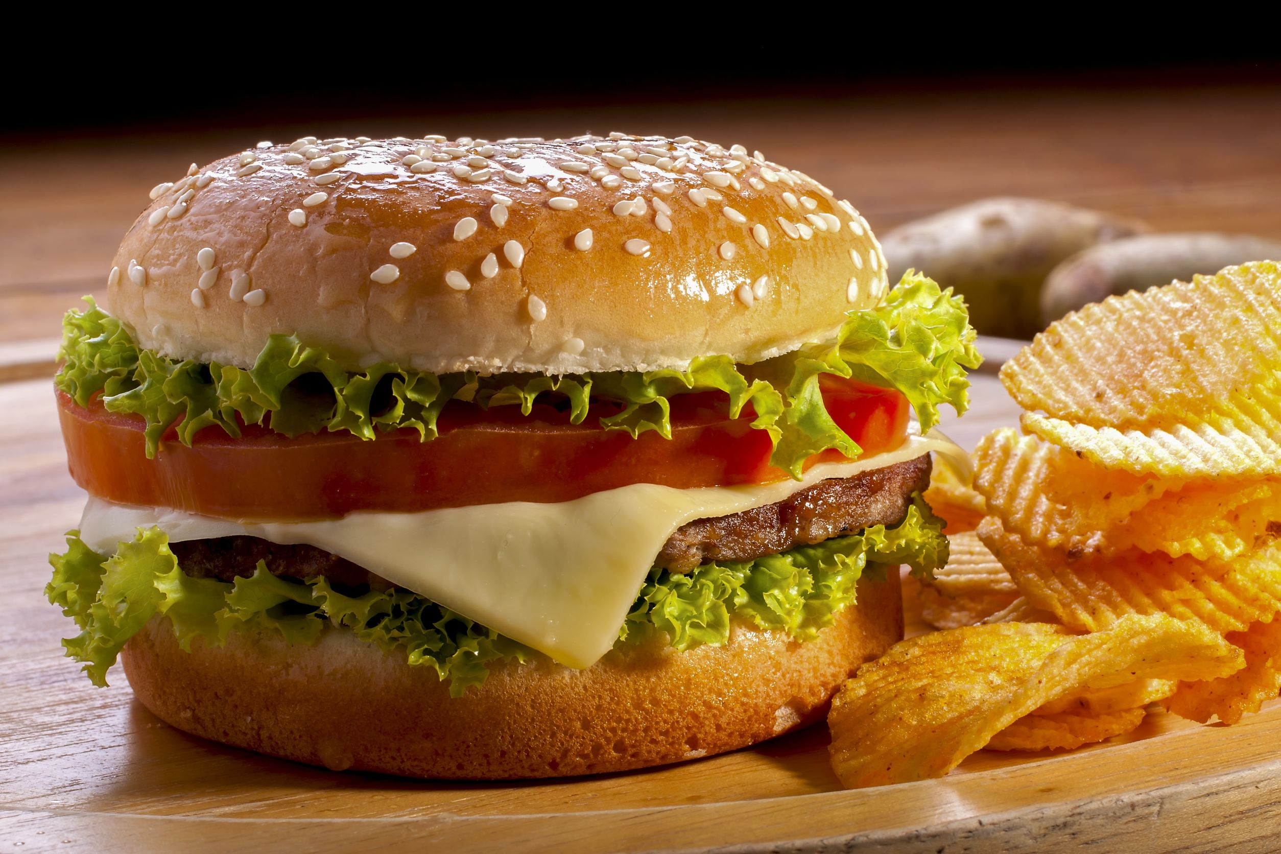 18225571 - burger with chips on wooden plates,and black background