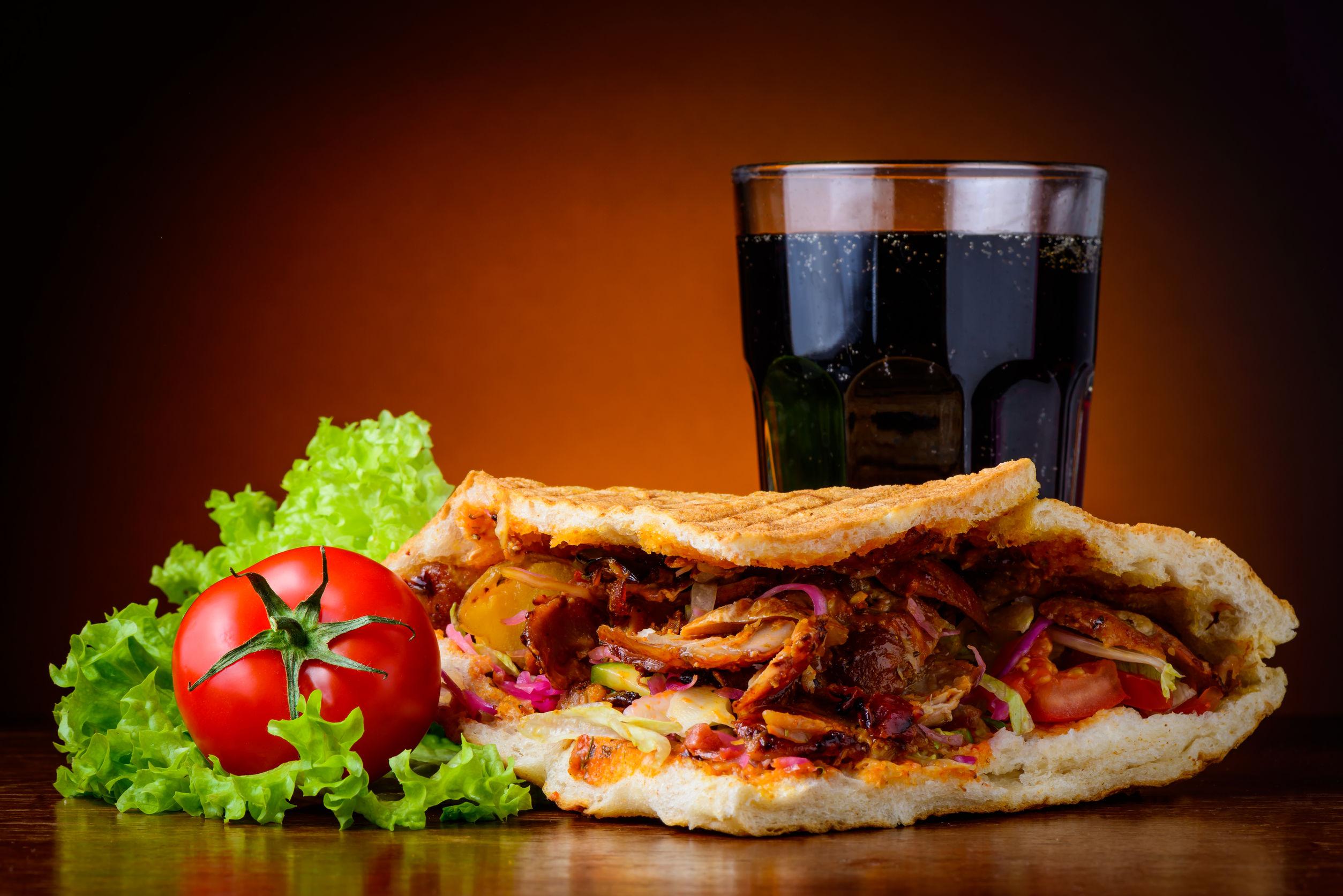 still life with doner kebab, fresh vegetables and cola drink